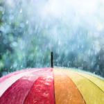 Picture is of a rainbow coloured umbrella with rain falling