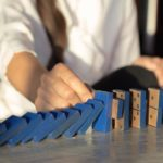 A photograph of a person knocking down wooden dominoes, which represents how business continuity acts like a domino effect of success