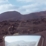 A picture of a side mirror giving a rear view of the road